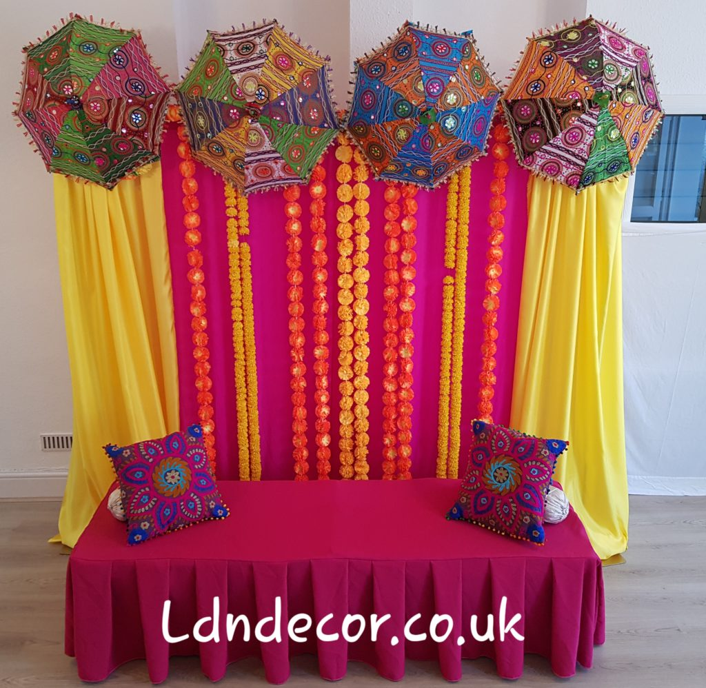 Colourful mehndi backdrip with garlands and umbrellas
